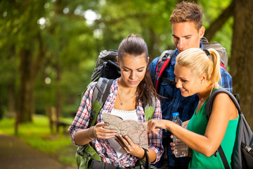Three hikers watching the map