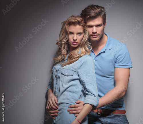 casual man holding his girlfriend close to him