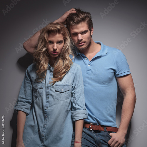 man with hand in his hair leaning against girlfriend