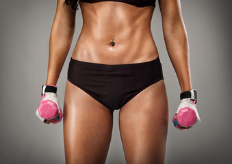strong female body with dumbbells