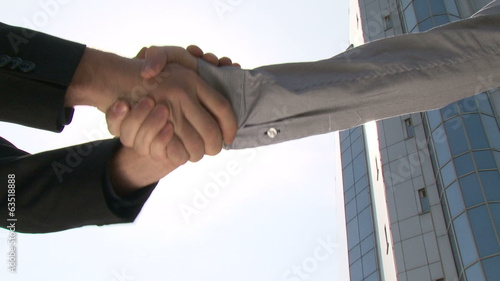 Two businessmen shaking hands in front of office building