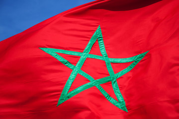 National flag of Morocco above blue sky