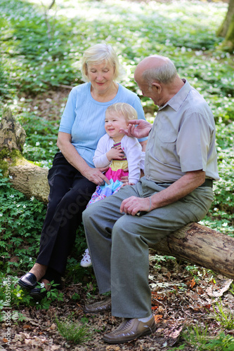Happy grandparents relaxing with granddaughter in summer forest