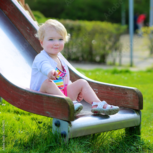 Happy child on playground sitting on the slide