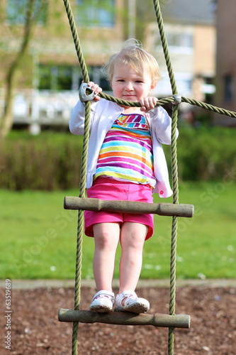 Little toddler girl on playground climbing on the net