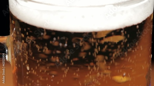 Pouring beer in glass on black background