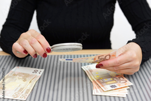 woman is looking through a magnifying glass for counterfeit mone