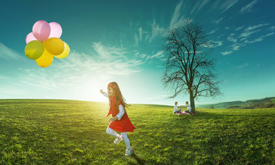 Happy girl running in a meadow with colorful balloons