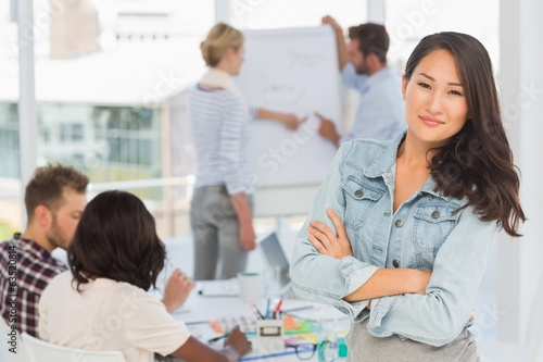 Asian woman smiling at camera while her colleagues are working