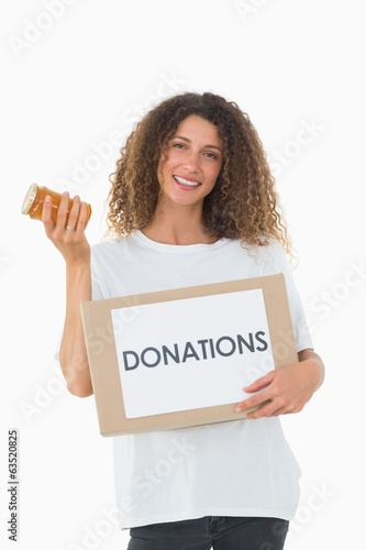Happy volunteer holding a box of donations and jam jar