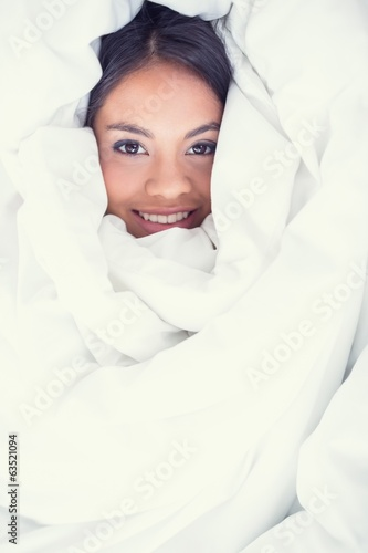 Pretty girl wrapped up in her duvet smiling at camera
