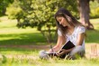 canvas print picture - Young woman with book and pen in park