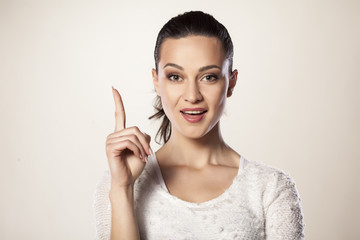 Happy and smiling young woman pointing a finger upwards