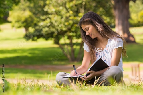 canvas print picture Young woman with book and pen in park