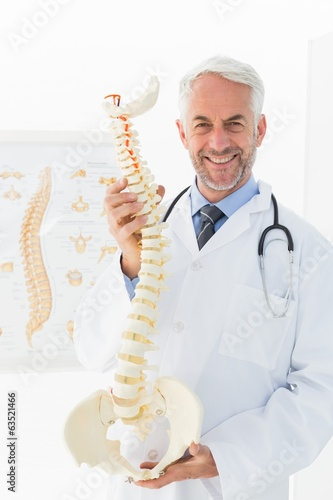 Confident mature male doctor holding skeleton model