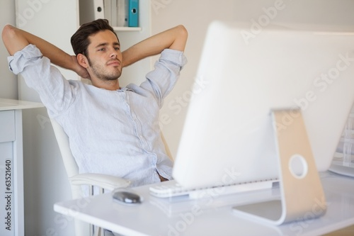 Casual businessman relaxing at desk leaning back
