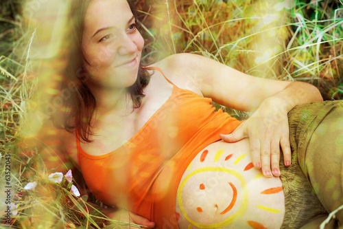 Pregnant woman portrait with drawing of smile.
