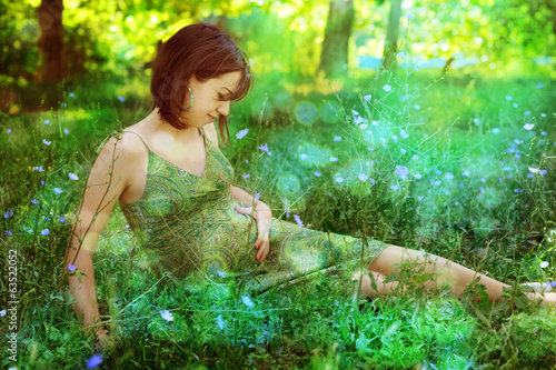 Pregnant woman relaxing on a romantic clearing.