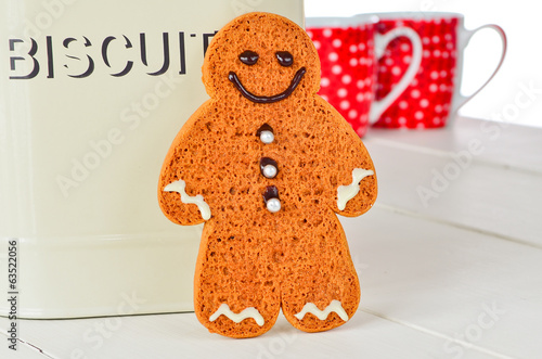 Home made ginger bread man with coffee cups and biscuit tin