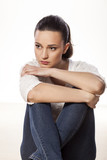 miserable and sad young woman sitting on a white background poster