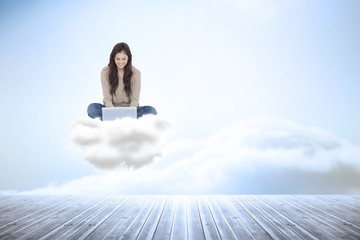 Composite image of brunette sitting on cloud using laptop