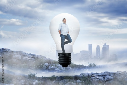 Composite image of thinking man in light bulb