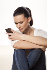miserable and sad young woman looking at her mobile phone