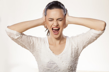 beautiful young woman is holding her head and screaming