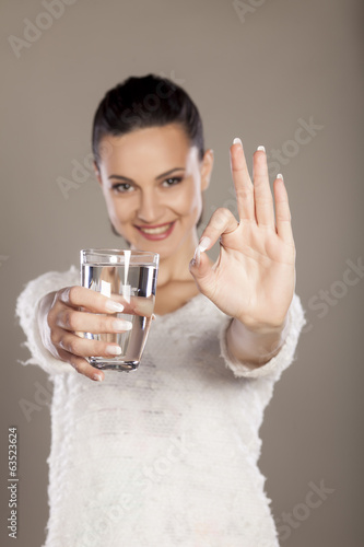 woman holding a glass of water and shows a sign for delicious