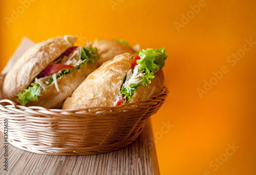 burgers in a basket on an orange background