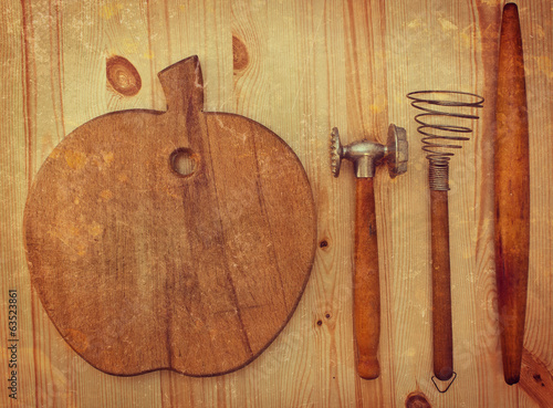 Old wooden kitchen utensils on a grungy wooden background