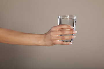 woman's hand holding a glass of clean water