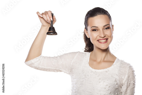 young smiling girl ringing a bell