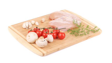 Raw chicken breast and vegetables