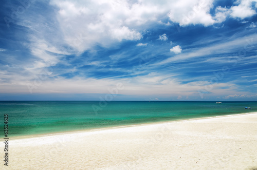 Clear water and blue sky. White sand beach