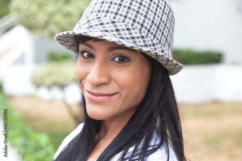 Brazilian woman with hat smiling at camera