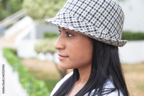 Attractive brazilian woman with hat looking sideways