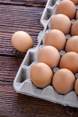 .eggs arranged in a cardboard on a wooden table