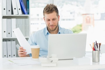 Happy man working at his desk on laptop
