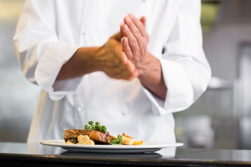 Mid section of a chef putting salt in kitchen
