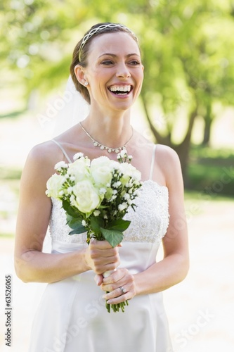 Bride holding bouquet while laughing in garden