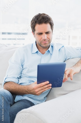 Handsome man sitting on the sofa using his tablet pc