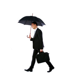 Businessman walking with umbrella and laptop bag