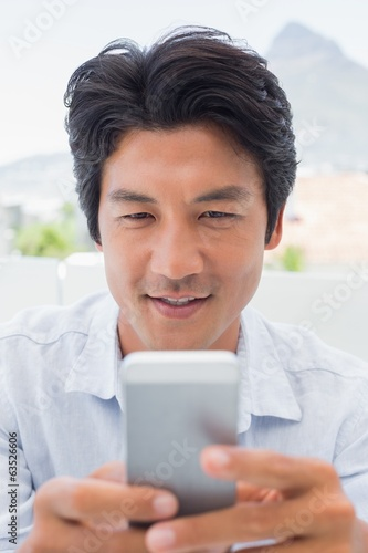 Smiling man sending a text message