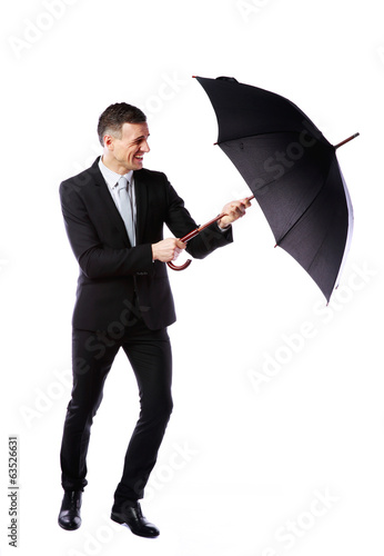 Businessman having fun with umbrella