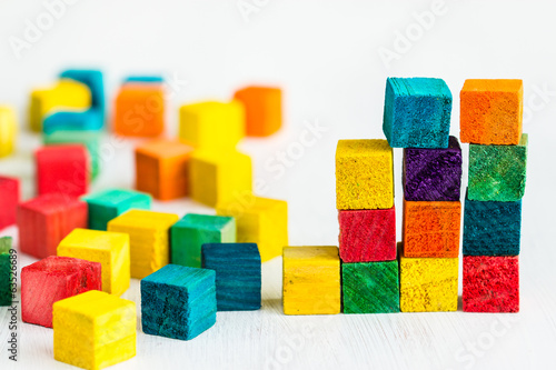 Colorful wooden building blocks on white background.