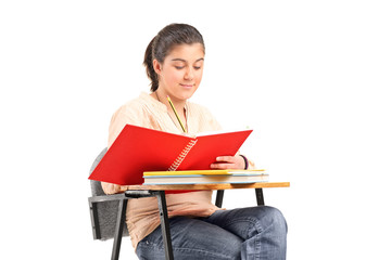 Girl writing in a notebook on school desk