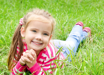 Portrait of adorable smiling little girl lying on grass