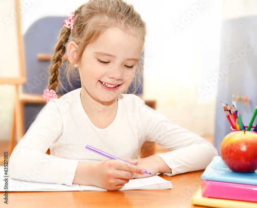 Cute little girl is writing at the desk  in preschool