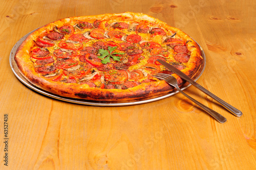 pepperoni pizza on the wooden table with knife and fork